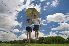 Jumping couple. A couple landing down with an umbrella after jumping up high in the outdoors Stock Photography