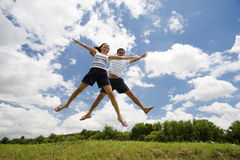 Jumping Couple. A cute couple jumping together in the outdoors, on green grass Royalty Free Stock Image