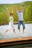 Jumping couple on a lake Royalty Free Stock Images