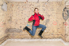 Jumping craftswoman with thumbs up in front of brick wall in bar Stock Image