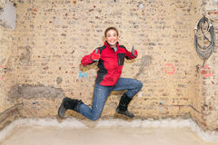 Jumping craftswoman with thumbs up in front of brick wall in bar Stock Images