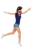Jumping Dancer Girl. Woman in blue shirt, jeans shorts white sneakers and red sun visor cap dancing on one leg with arms outstretched. Full length studio shot Royalty Free Stock Image