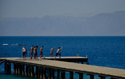 Jumping from the deck. People are jumping from a deck in the red sea next to aqaba, Jordan Royalty Free Stock Photos