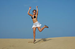 Jumping in the desert. Young woman enjoying hers vacation in the desert Stock Photo