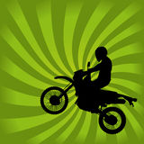 Jumping Dirt Bike Silhouette. On a Green Swirl Background Royalty Free Stock Photo