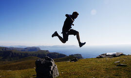 Jumping at the dramatic Cape Vestkapp Stock Images