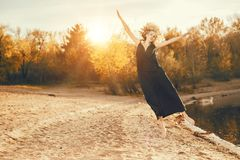 Jumping and enjoying. A beautiful young girl is posing outside in a black dress. Fashion concept royalty free stock photo