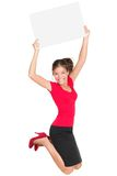 Jumping excited woman showing sign. Sign woman jumping excited and happy showing blank empty sign card with copy space for your text. Beautiful smiling young Stock Photos