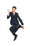 Jumping executive showing okay sign Stock Photo