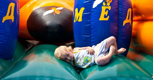 Jumping and falling on bouncy castle Stock Image