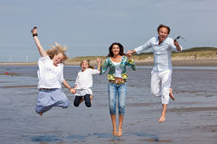 Jumping family. Happy family with two kids jumping in the air on the beach Royalty Free Stock Photo