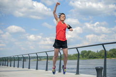 Jumping fit woman with arms up. Stock Photography