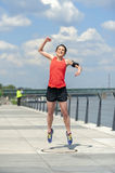 Jumping fit woman with arms up. Stock Image