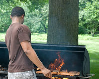Jumping from The Flames 1. Man jumps back as flames engulf the hamburgers and hotdogs Stock Photography