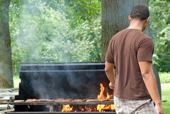 Jumping from The Flames 3. Man jumps back as flames engulf the hamburgers and hotdogs Stock Photos