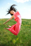 Jumping and flying graceful girl on the background of blue sky Stock Image