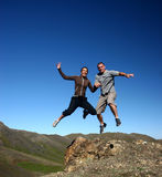 Jumping fpr joy. Married couple jumping in Mongolia royalty free stock photography
