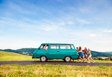 Jumping frieds with campervan, green nature and blue sky stock photography