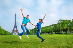 Jumping in front of the Eiffel Tower. Excited young couple jumping in front of the Eiffel Tower in Paris Stock Photo