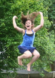 Jumping for Fun. Young girl having fun jumping in the air Royalty Free Stock Images
