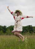 Jumping girl. In flowers wreath  and traditional clothes against clouds Royalty Free Stock Images
