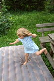 Jumping girl. A girl jumping from a garden bench on to a inflatable mattress Royalty Free Stock Image