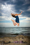 Jumping girl. Young beautiful girl jumping gracefully at the beach with beautiful sky in the background Royalty Free Stock Photography