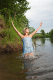 Jumping girl. In flower chaplet at river Royalty Free Stock Images