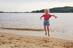 Jumping girl. Little girl in colour clothes jumps on the bank of lake stock photo