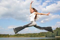 Jumping girl. Happy jumping girl on the water royalty free stock photos