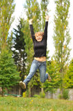 Jumping girl. Girl jumping in the park and lookin in the camera Stock Photo