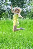 Jumping girl. In yellow against summer meadow Royalty Free Stock Photo