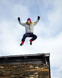 Jumping girl. Girl jumping from a roof into snow Stock Images
