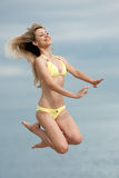 Jumping girl. Attractive young woman in yellow swimsuit jumping on the background of the sea Royalty Free Stock Photo