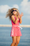 Jumping girl. Attractive young woman in red dress jumping on the background of the sky Royalty Free Stock Image