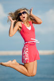 Jumping girl. Attractive young woman in red dress jumping on the background of the sky Stock Photo
