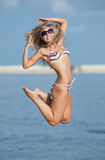 Jumping girl. Attractive young woman in swimsuit jumping on the background of the sky Royalty Free Stock Image