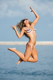 Jumping girl. Attractive young woman in swimsuit jumping on the background of the sky Royalty Free Stock Images