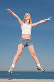 Jumping girl. Vigorous blond woman in shorts and white shirt is jumping outdoors Royalty Free Stock Photos