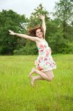 Jumping girl. Against summer meadow in summer day Stock Photo