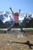 Jumping girl. And mountains with blue sky in the background Royalty Free Stock Images