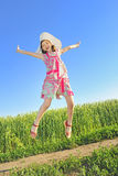 Jumping girl. In summer time on field Royalty Free Stock Image