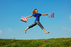Jumping Girl. Jump girl with bags on the meadow royalty free stock images