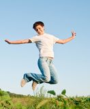 Jumping girl. Pretty young woman jumping on green grass Stock Photography