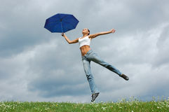 Jumping girl. On meadow with an umbrella stock photos