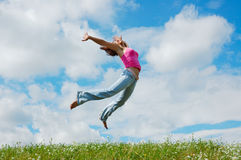 Jumping girl. On the green meadow royalty free stock image