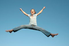 Jumping girl. Young girl jumping in a blue sky Stock Photography