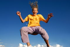 Jumping girl. Girl jumping high in midair with blue sky behind her Stock Photos