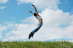 Jumping girl. On the green meadow Royalty Free Stock Photo