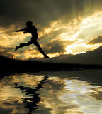 Jumping girl. A jumping girl on the sunset background royalty free stock photo
